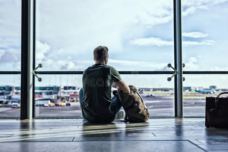 Hipster man sitting in airport stock photography