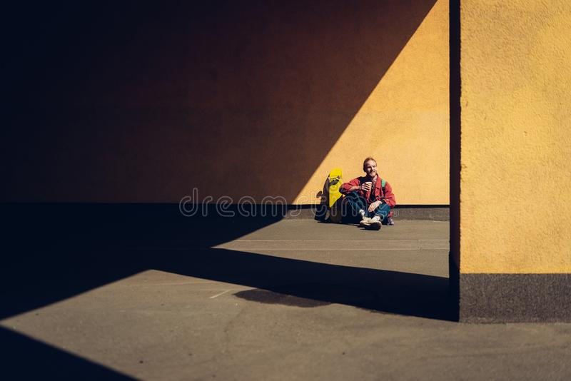 Hipster man sitting with skateboard and coffee. Urban lifestyle and activity. Full length portrait of young smiling hipster guy sitting on ground outdoor with royalty free stock image