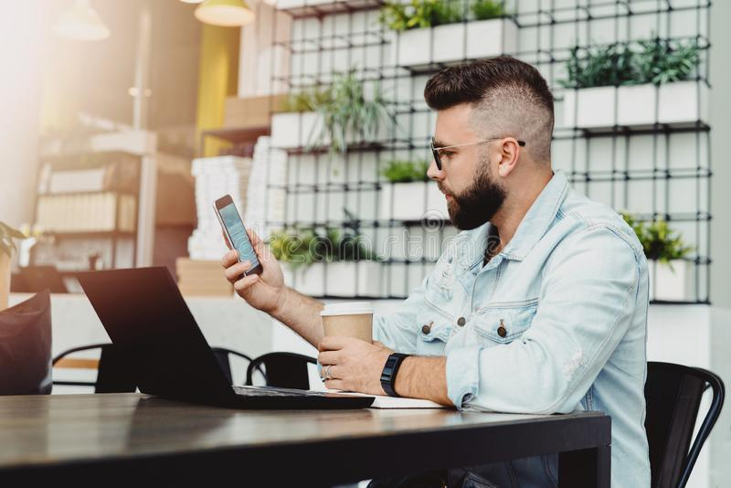 Hipster man with smartphone in his hand, sitting in cafe at lunchtime and drinking coffee. On table is laptop and notebook. royalty free stock photos
