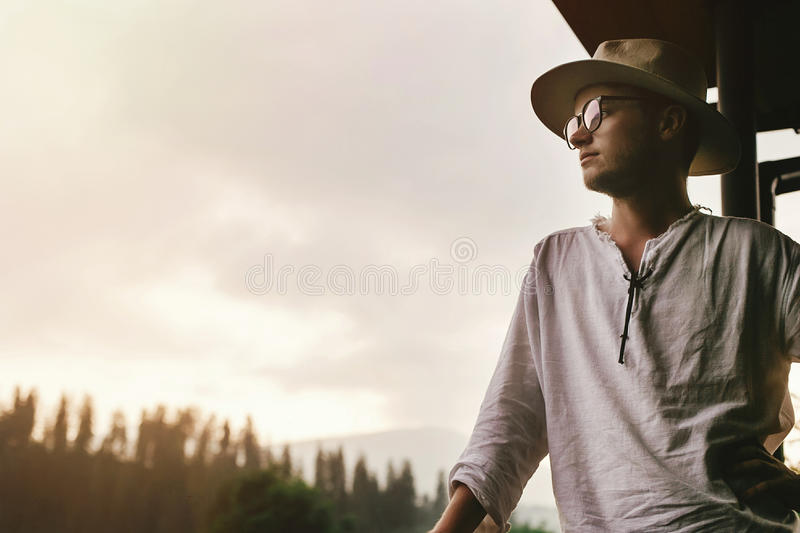 Hipster man standing on porch of wooden house looking at mounta royalty free stock photography