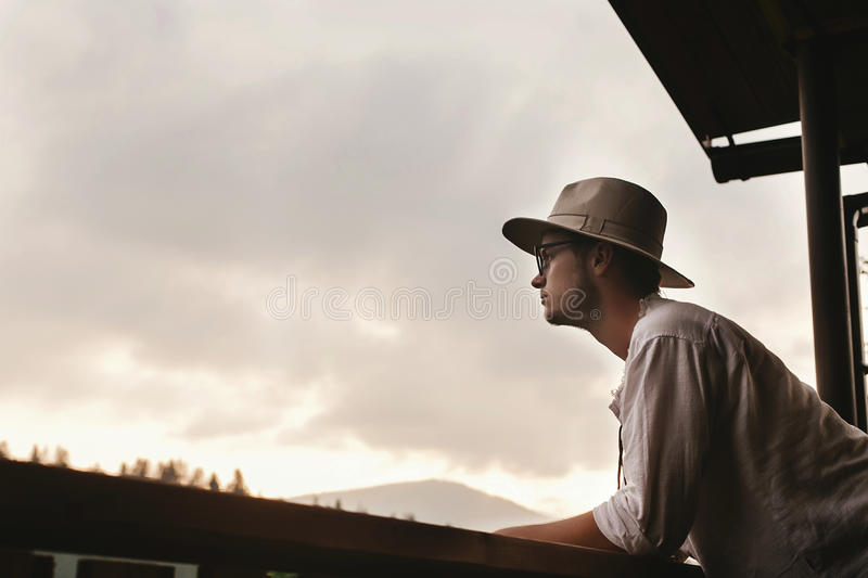 Hipster man standing on porch of wooden house looking at mounta stock photography