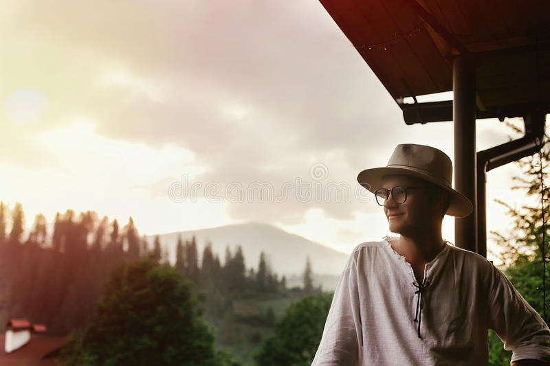 Hipster man standing on porch of wooden house looking at mounta stock photo