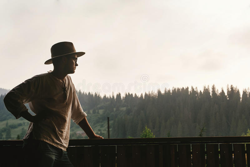 hipster man standing on porch of wooden house and relaxing looking at mountains in evening, calm moment, summer vacation royalty free stock photography
