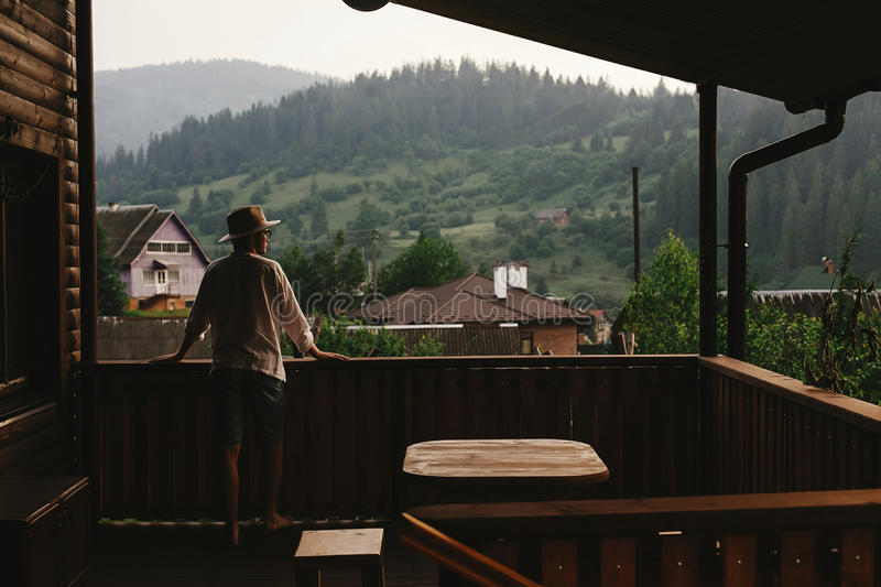 hipster man standing on porch of wooden house and relaxing looking at mountains in evening, calm moment, summer vacation royalty free stock photos