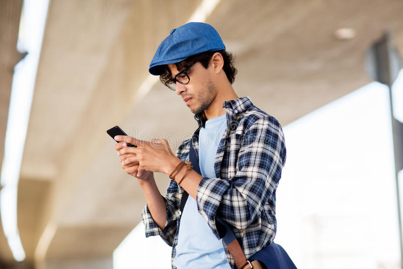 Hipster man texting message on smartphone royalty free stock images