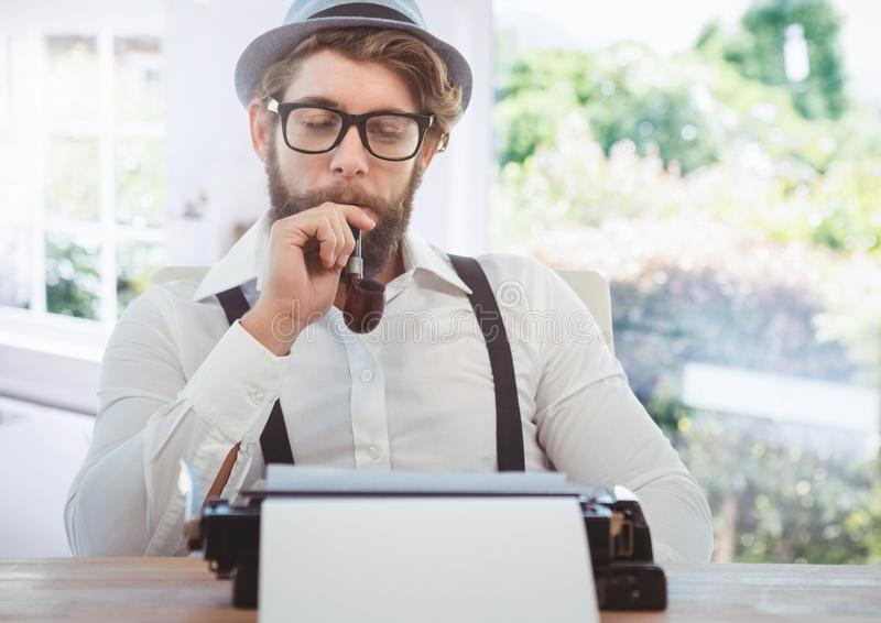 Hipster man on typewriter with bright windows royalty free stock photography