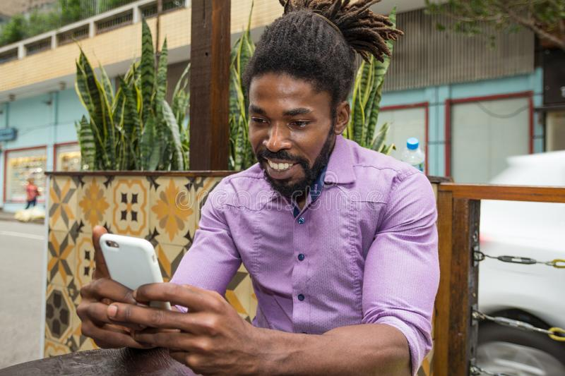 Hipster man using cell phone to check social media and browse in the internet with mobile device. Black man using cell phone to check social media and browse in royalty free stock photography