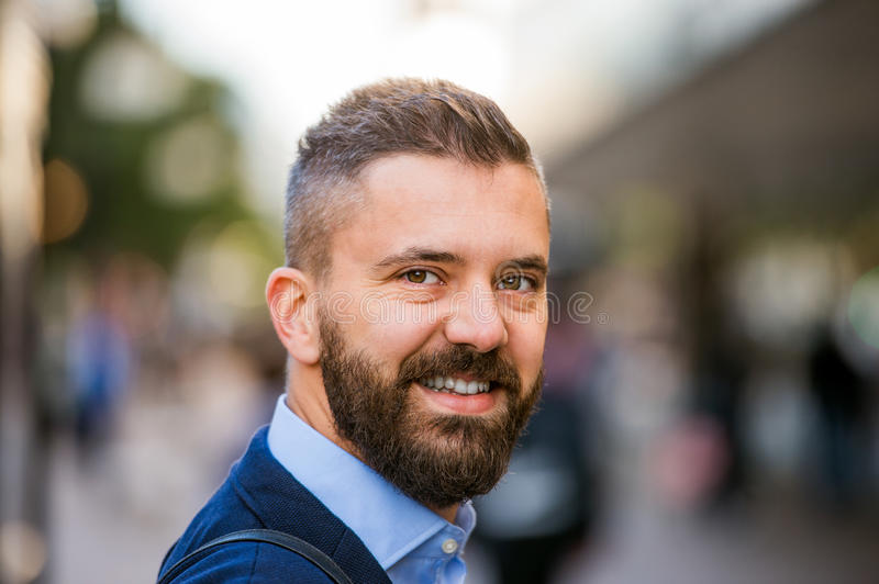 Hipster manager in blue shirt walking in the street royalty free stock images