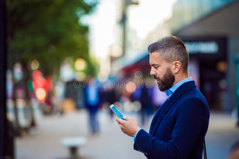 Hipster manager holding smartphone, texting outside in the street stock photo