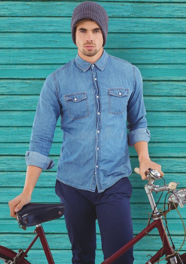 hipster med cykeln som är främst av ljus - blå wood bakgrund arkivbild