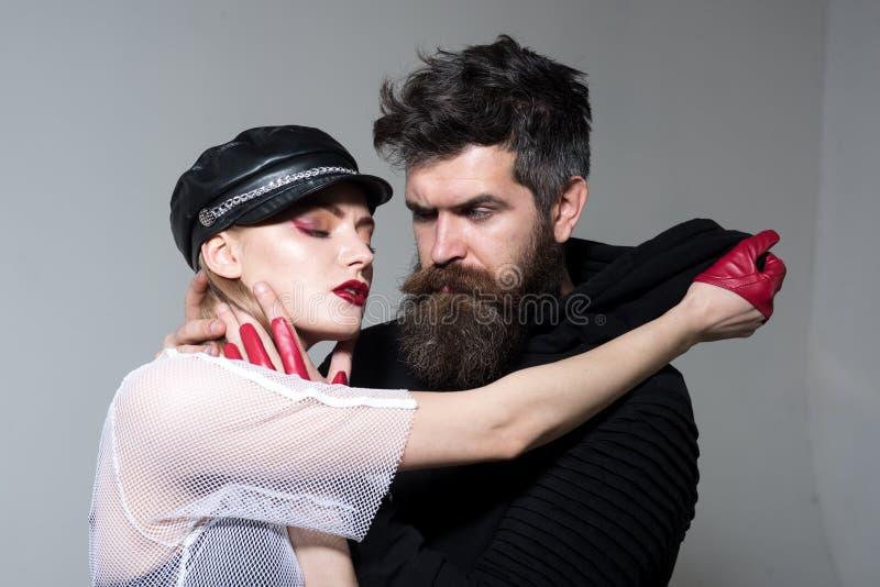 Hipster med skägget och flicka i läderlock och handskar koppla ihop förälskat av den sexiga kvinnan och den skäggiga mannen vagga royaltyfri fotografi