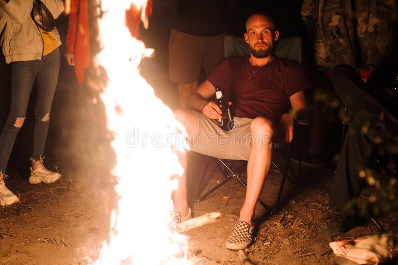 Hipster man drinking beer and relaxing with friends travelers at big bonfire at night camp in the forest. Group of people resting royalty free stock photo