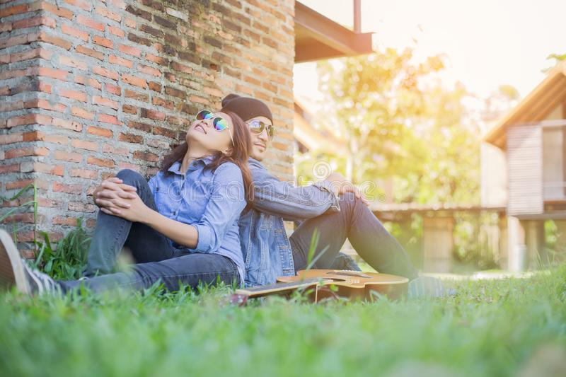 Hipster man playing guitar for his girlfriend outdoor against brick wall, enjoying together. Hipster men playing guitar for his girlfriend outdoor against brick royalty free stock image