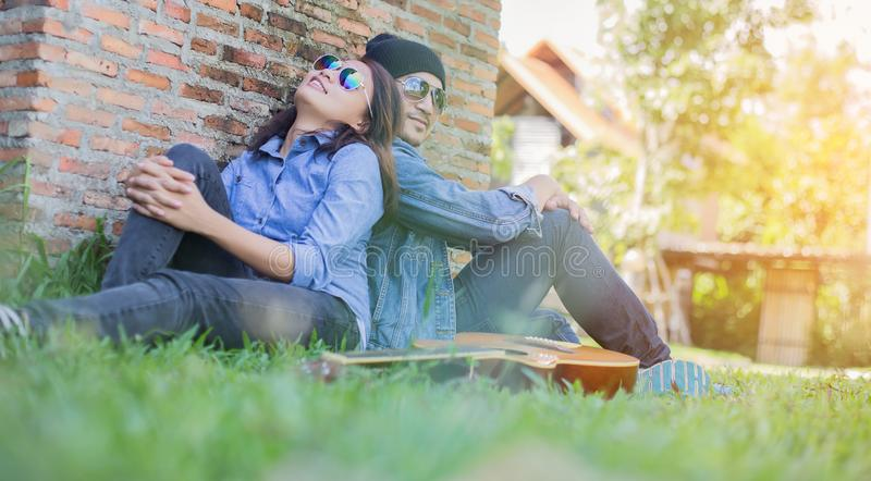 Hipster man playing guitar for his girlfriend outdoor against brick wall, enjoying together. Hipster men playing guitar for his girlfriend outdoor against brick stock photos