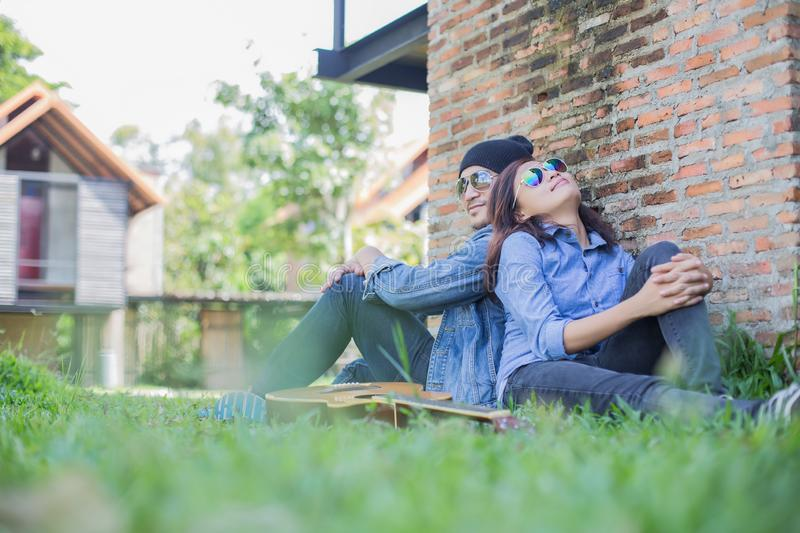 Hipster man playing guitar for his girlfriend outdoor against brick wall, enjoying together. Hipster men playing guitar for his girlfriend outdoor against brick royalty free stock images
