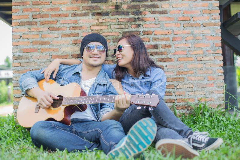 Hipster man playing guitar for his girlfriend outdoor against brick wall, enjoying together. Hipster men playing guitar for his girlfriend outdoor against brick stock photography