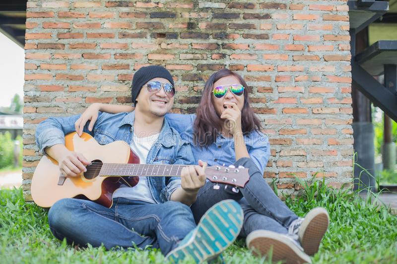 Hipster man playing guitar for his girlfriend outdoor against brick wall, enjoying together. Hipster men playing guitar for his girlfriend outdoor against brick royalty free stock photo