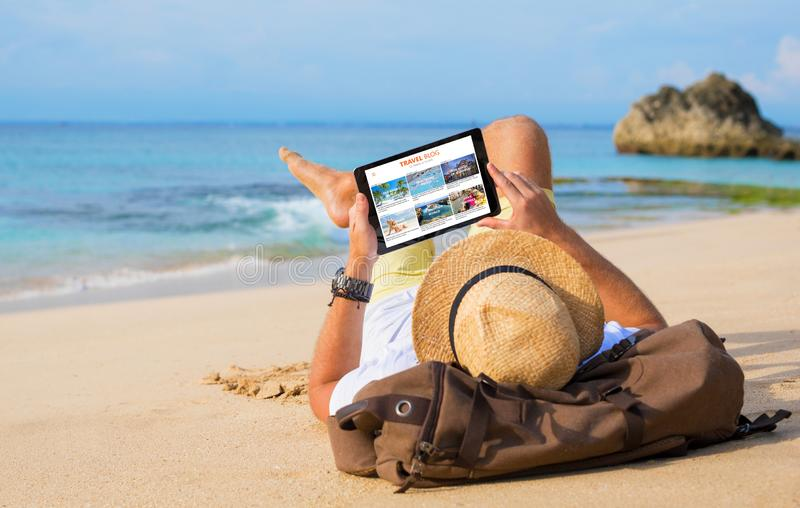 Man reading travel blog on beach stock image