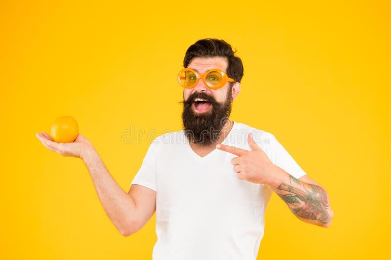 Hipster met baard in de zomerstemming De vrolijke rijpe oranje citrusvruchten van de kerelgreep De vakantie van de zomer Mensen g stock foto
