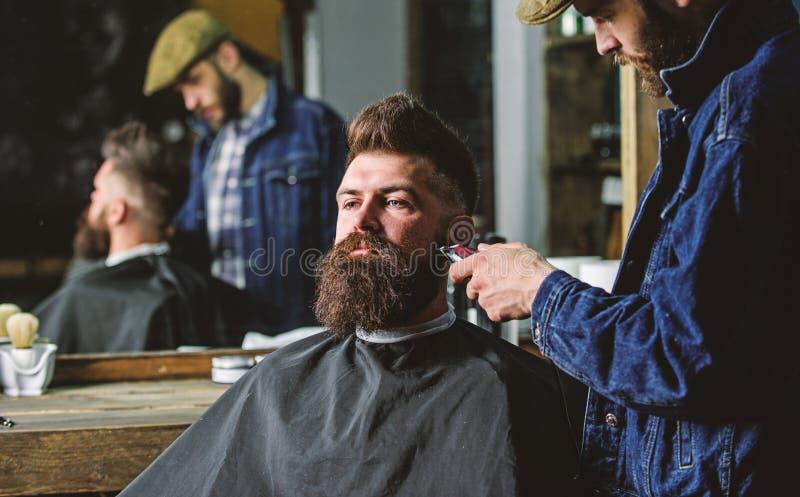 Hipster met baard die met kaap het in orde maken door professionele kapper in modieuze herenkapper wordt behandeld Het verzorgen  stock foto