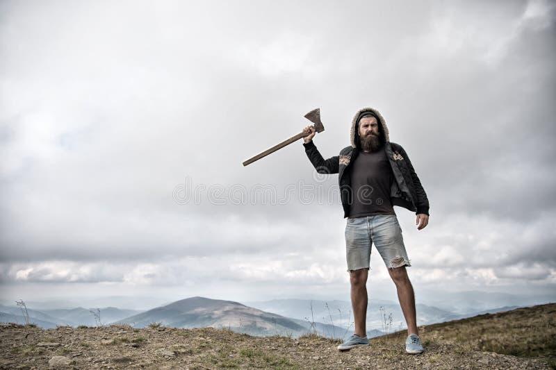 Hipster met baard houdt bijl terwijl tribune bovenop berg, hemel op achtergrond, exemplaarruimte Brutale houthakker en stock foto's