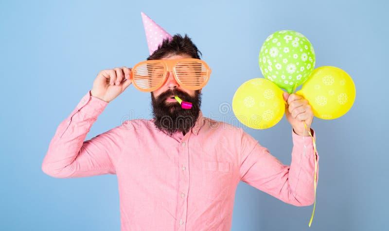 Hipster met dichtbegroeide baard het vieren verjaardag Het gebaarde mens stellen in verjaardag GLB met enorme glazen en helder stock afbeelding