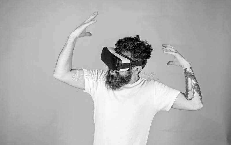 Hipster met ge?nspireerde uitdrukking die VR met modern gadget onderzoeken vr gadgetconcept Kerel met hoofd opgezette vertoning stock afbeelding