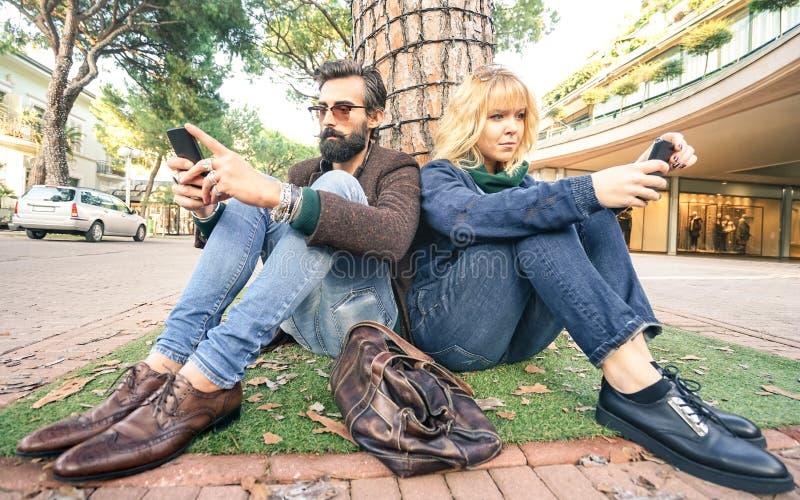 Hipster millennial paar in disinterest ogenblik met smartphone - Apathieconcept over droefheid en isolatie die mobiele telefoon m stock afbeeldingen