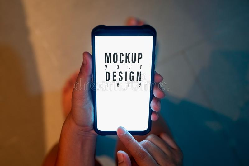 Hipster mockup image of woman`s hand holding modern mobile smartphone with blank screen for text message or advertisement content stock photography