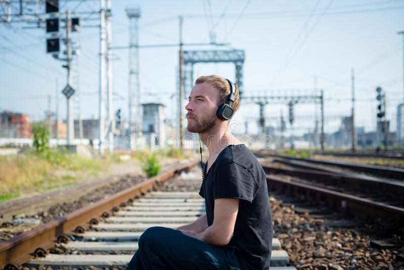 Hipster modern stylish blonde man on rails. In daily life stock photo