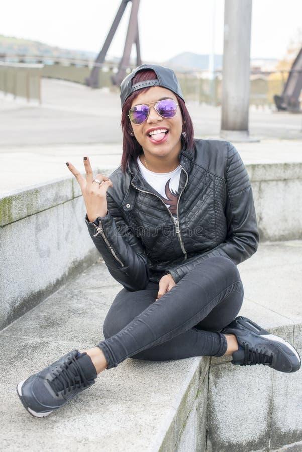 Hipster mooie jonge vrouw die haar tong tonen stock fotografie
