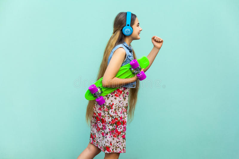 Hipster in motion on light blue background. The young happy beautiful long haired blonde girl in dress and headphones stock photos