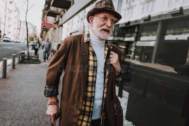 Hipster old man walking in the city stock images