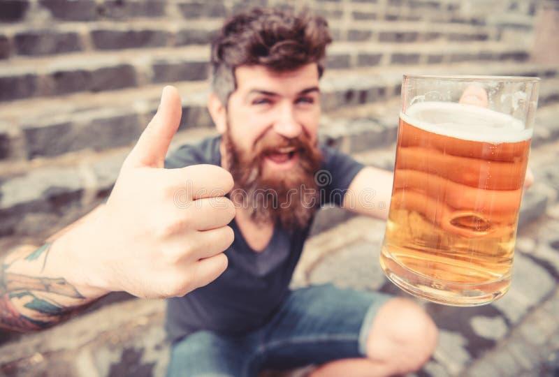 Hipster op vrolijk gezicht drinkt bier Bier van het vatconcept Kerel die rust met bier hebben, selectieve nadruk Mens met baard stock foto's