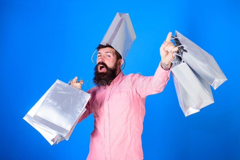 Hipster op vrolijk gezicht met zak op hoofd is gewijde shopaholic De mens met baard en snor draagt het winkelen zakken stock foto