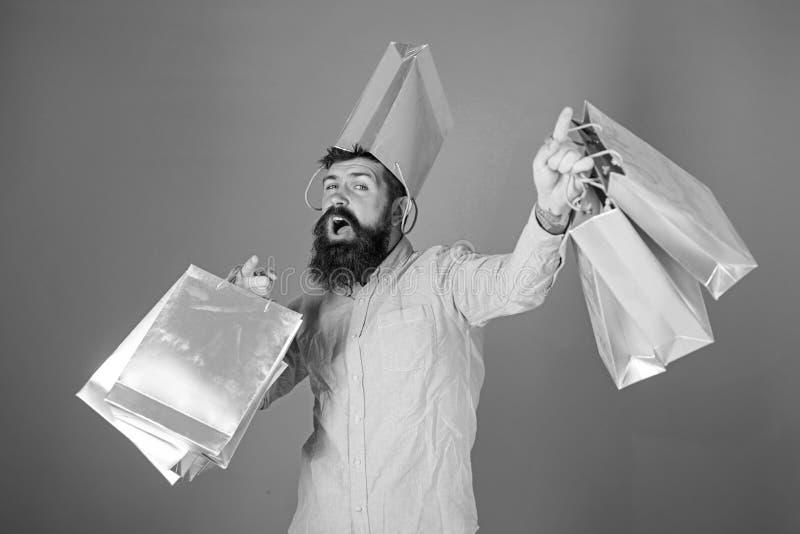 Hipster op vrolijk gezicht met zak op hoofd is gewijde shopaholic De mens met baard en snor draagt het winkelen zakken stock afbeelding