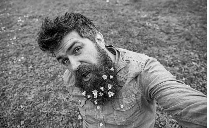 Hipster op vrolijk gezicht zit op gras, defocused De mens met baard geniet van de lente, groene weideachtergrond Natuurlijke Scho royalty-vrije stock afbeeldingen