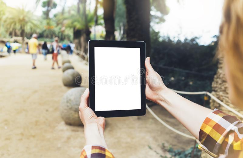 Hipster person holding in hands digital tablet with empty blank screen, girl photograph on computer against a background nature royalty free stock photography