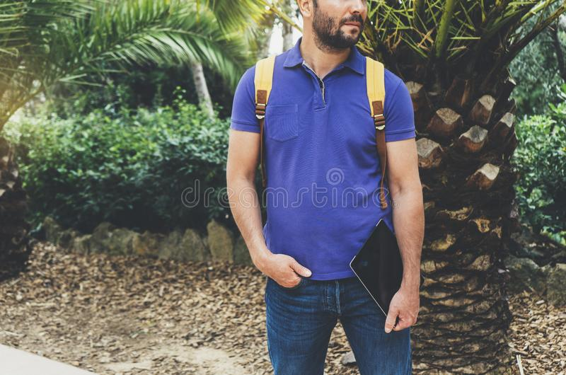 Hipster person holding in male hands digital tablet with blank screen, front view guy standing in shirt with computer on back royalty free stock images