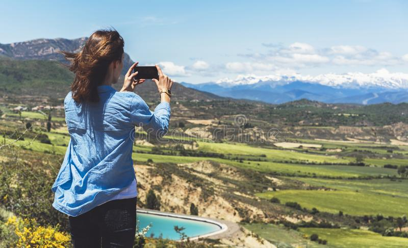 Hipster photograph on smart phone gadget mobile, mock up of blank screen. Girl traveler hold in hand mobile on background mountain royalty free stock photo