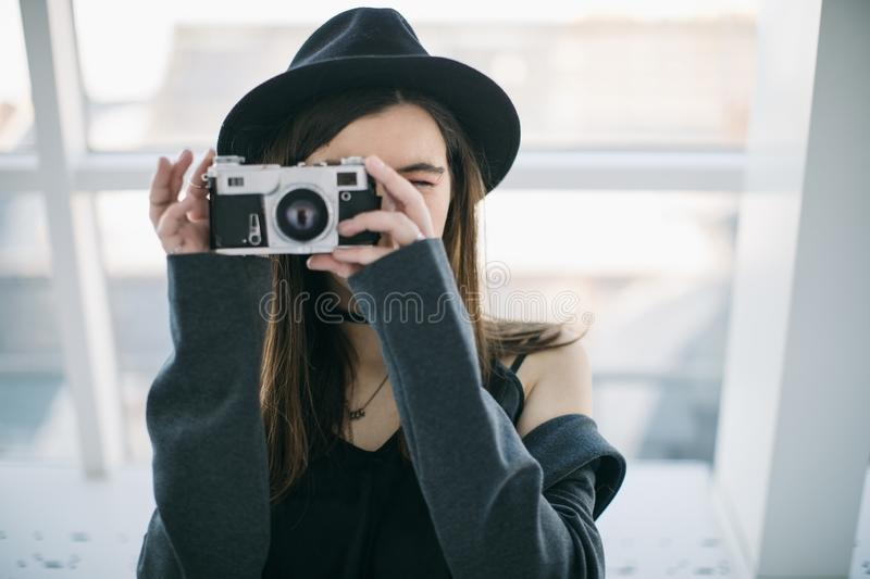 Hipster photographer teen girtl. Stylish casual clothes with hat. Creative education stock photo
