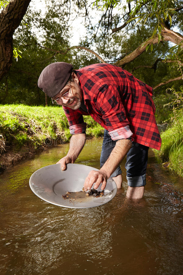 Hipster prospector panning sand in creek for gold. Contemporary lucky prospector found lot of gold in creek when panning sand stock photos
