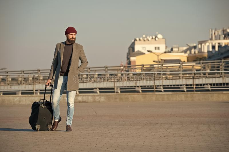 Hipster ready enjoy travel. Carry travel bag. Man bearded hipster travel with luggage bag on wheels. Traveler with royalty free stock image