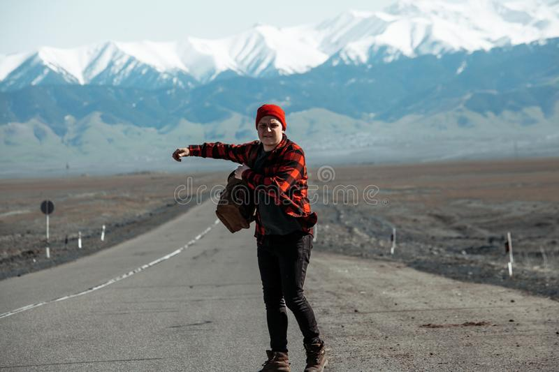Hipster in red hitchhiking on old dusty road. Hipster dressed in red flannel shirt hitchhiking down on old dusty road royalty free stock image