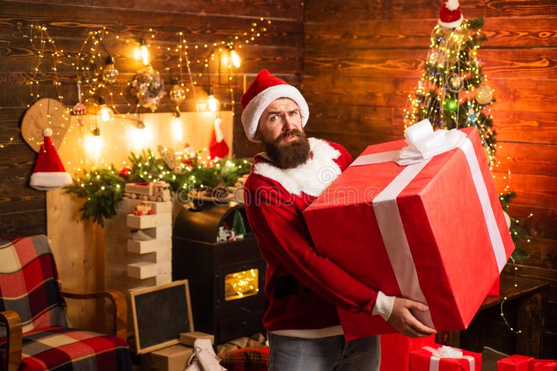 Hipster in red Santa hat holding present. Delivery gifts. Gift emotions. Merry Christmas and Happy Holidays. Santa man stock photography