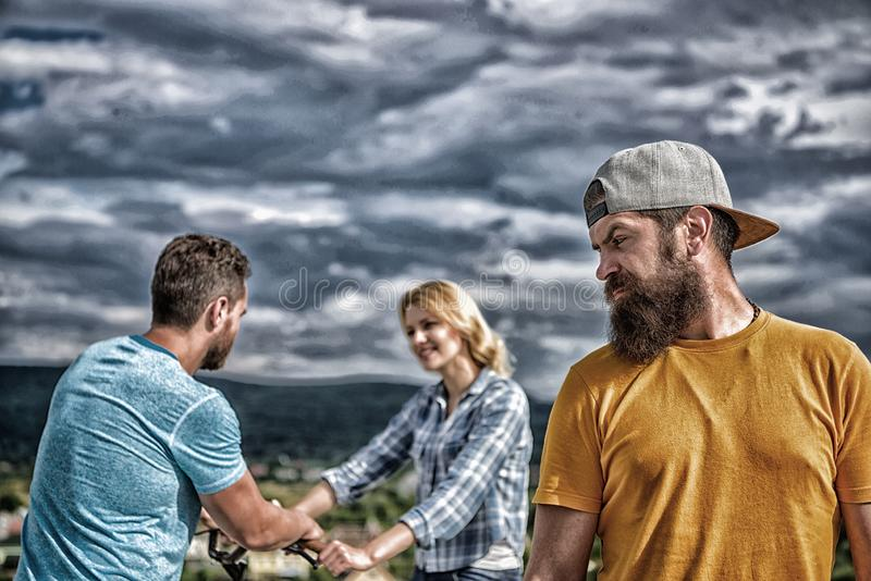 Hipster regretful face in front of couple in love. Man hipster feels lonely couple dating behind him. No romantic in his royalty free stock photo