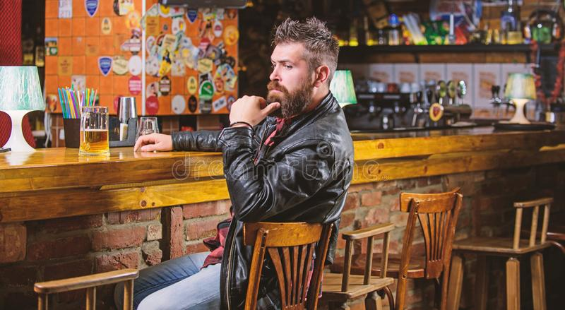 Hipster relaxing at bar with beer. Bar is relaxing place to have drink and relax. Man with beard spend leisure in dark. Bar. Brutal hipster bearded man sit at stock photography