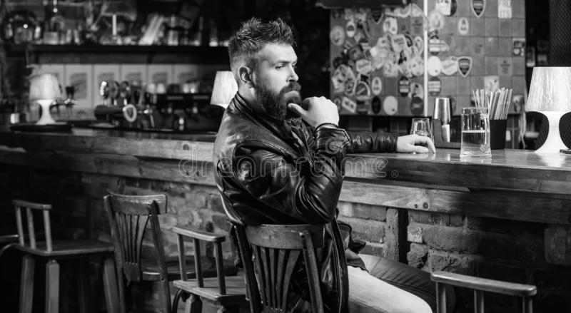 Hipster relaxing at bar with beer. Bar is relaxing place to have drink and relax. Man with beard spend leisure in dark royalty free stock images