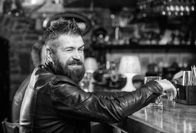 Hipster relaxing at bar with beer. Brutal hipster bearded man sit at bar counter drink beer. Order alcohol drink. Bar is stock photography