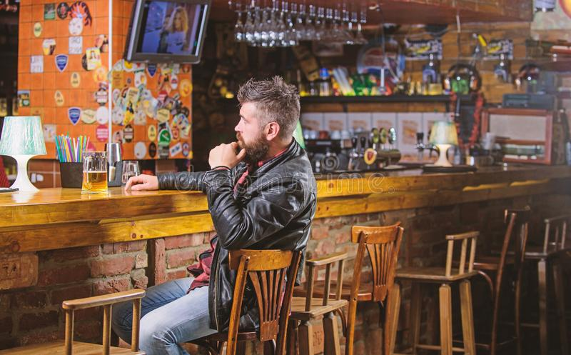 Hipster relaxing at bar with beer. Man with beard spend leisure in dark bar. Brutal hipster bearded man sit at bar stock image